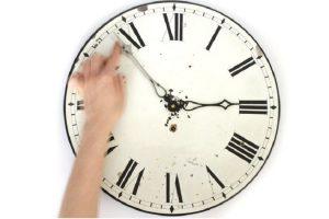 دست فردی که دارد ساعت را جلو میکشد