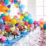 میز جشن تولد همراه با گل صورتی طبیعی و بادکنکهای رنگارنگ