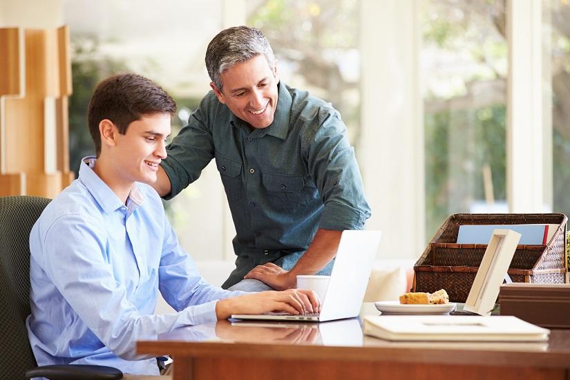 پدر و فررزند به لپتاپ نگاه میکنند.