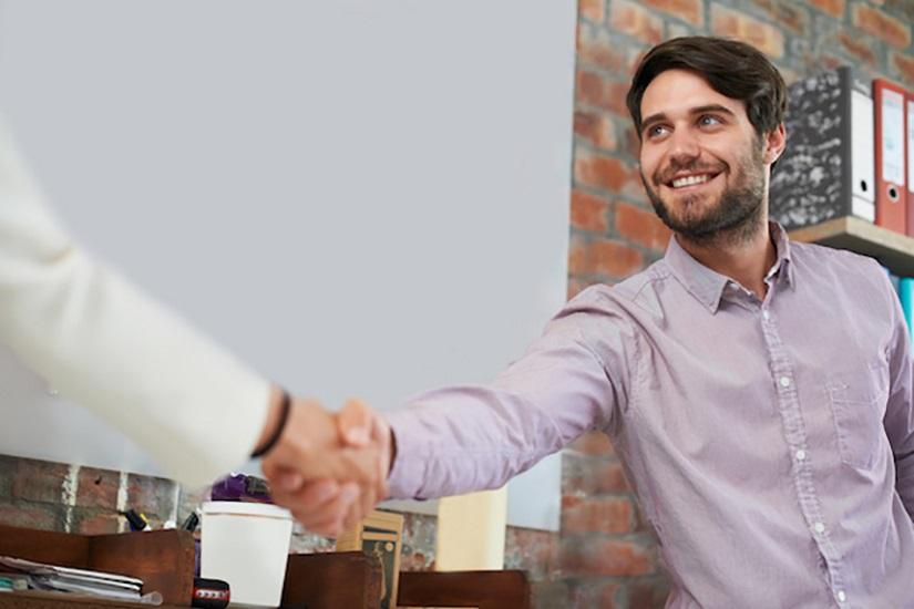 مرد جوان تاجر با یک نفر دست میدهد.